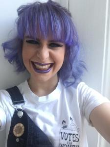 Selfie of Hazel smiling with purple hair.